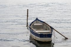 Rowboat docked on the water next to a wooden plank stock image