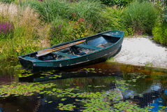 Rowboat in a garden pond Royalty Free Stock Image