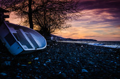 Rowboat Left On The Pebble Shore Sunset Stock Photography