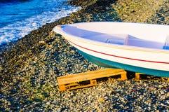 Rowboat Left On The Pebble Shore Sunset Stock Image