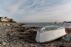 Rowboat on the shoreline of a harbor. Rowboat on the rocky shoreline of a New Hampshire harbor under a partly cloudy sky Stock Images