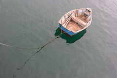 Rowboat on a rope. Lonely row boat tugging on a rope royalty free stock photography