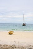 Rowboat and sailboat. White rowboat landing on beach and white sailboat is mooring in the sea.Picture from Koh Samet, Thailand Stock Photo
