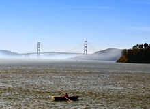 Rowboat, San Francisco Bay, California. The Golden Gate Bridge is seen through a light fog by a man in a rowboat in San Francisco Bay from Tiburon in Marin Royalty Free Stock Photo