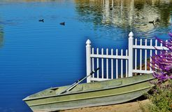 A rowboat on the shore of a lake. An old rowboat sitting on the shore of a pristine lake next to a white picket fence Stock Photo