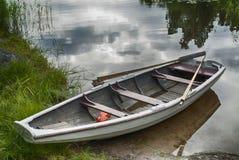 Rowboat at shore. A wooden rowboat at shore by a lake Royalty Free Stock Images