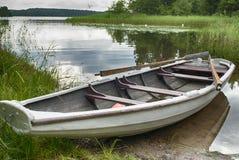 Rowboat at shore. A wooden rowbat at shore by a lake Royalty Free Stock Photo