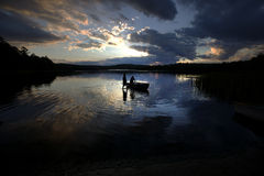 Rowboat silhouette in lake Royalty Free Stock Photos