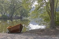 Rowboat Waiting By a Still Lake Stock Photos