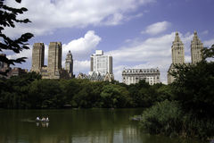 Rowboating in Central Park. A view of a rowboat in Central Park on a beautiful summer day with a bright blue sky and Central Park West buildings in the stock photos