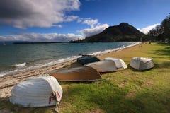 Mount Maunganui, New Zealand. Rowboats on the beach stock image