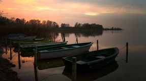 Rowboats on the lake shore after sunset, scenic landscape with copy space stock photo