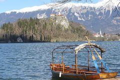 Rowboats moored on the shore of Lake Bled and medieval castle Royalty Free Stock Photography