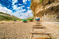 Rowboats storage  in Italy. Rowboats storage  on the stony and pebble beach in Italy Royalty Free Stock Images