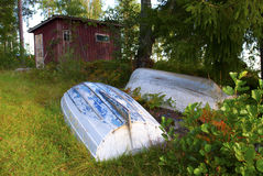 Rowboats in front of red shed. Rowboats turned upside down for winter storage Royalty Free Stock Photos