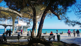 Сrowded Yalta embankment in Sunny winter day Stock Photos