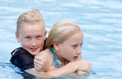 Rowdy Boy Holding Girl in Pool Water. Eleven year old boy holding arms tightly around a 10 year old girl in a pool, both in bathing suits Royalty Free Stock Photo
