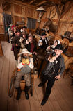 Rowdy Crowd with Guns in Saloon. Rowdy customers in old west saloon firing their guns Stock Photography