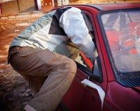 Rowdy, der in das Auto einbricht Stockfoto