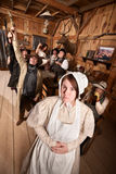 Rowdy Drinkers with Quiet Lady. Modest young women with group of drunks in saloon Stock Photography