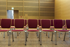 Rowed chairs in a wooden concert hall. Red padded chairs ready for seating in a concert hall Royalty Free Stock Image