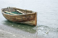 Rowed to shore. Old weathered row boat resting on shore Royalty Free Stock Images