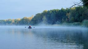 Rower. Anglers fishing early in the morning on the misty river. Dnipro river. Ukraine. Early autumn Royalty Free Stock Photo