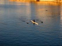Rower en el río en la puesta del sol foto de archivo
