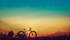 Rower górski sylwetka na pięknym zmierzchu, sylwetki fatbike Zdjęcie Stock