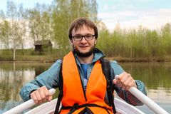 Rower man in the lifejacket in the boat. On the country Royalty Free Stock Image