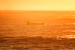 Rower in ocean at sunrise Royalty Free Stock Photo