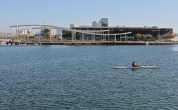 Rower Port Vell Barcelona Spain. Barcelona, Spain - March 9. Rower in a single scull on the port Vell with the Rambla del Mar on the background, Barcelona, Spain Stock Images