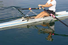 Rower. A young rower in a boat, paddles on the tranquil lake Stock Images