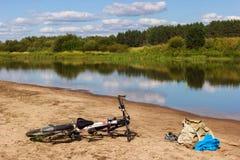 Rowerowy camping na rzecznej plaży Gorący letni dzień dla pływania, natura krajobrazu i odbić w wodzie, zdjęcie royalty free