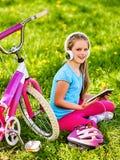 Rowerowy dziecko jest ubranym słuchawki słuchającą muzykę Bawić się na pastylka komputerze osobistym zdjęcia royalty free
