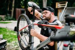 Rowerowy mechanik przystosowywa z narzędzie roweru siedzeniem obraz royalty free