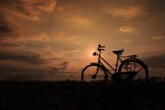 Rowerowy stawiający up przy drewnianym ogrodzeniem w wschodzie słońca Obrazy Stock