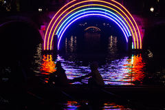 Rowers pass an artwork in a canal on the boat route Water Colors during the Amsterdam Light Festival 2016 Royalty Free Stock Photos