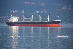 Rowers Pass Cargo Freighter in Vancouver Harbor Stock Image