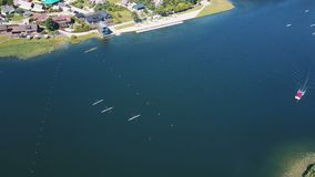 Rowers training aerial. People paddle among islands on a lake. Sparkling blue Water on a Sunny Day. Aerial view of. Aerial view of rowers training on a lake near stock video