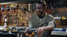roweru naprawianie Mężczyzna z brodą tworzy obyczajowego motocykl zbiory