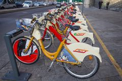 Roweru udzielenia usługa stojaki w Mediolan Koloru żółtego Bikemi bicykle są dostępni dla wynajem z transportu publicznego bilete obraz royalty free
