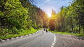 Rowerzyści na górzystej autostradzie, rowerzysta na drodze w zmierzchu światła jazdie na koszowej drogowej przepustce przez Alpej fotografia royalty free