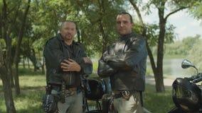 Rowerzyści z ręka krzyżuję pozować blisko motocyklu zbiory