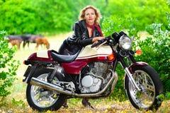 Rowerzysta dziewczyna w skórzanej kurtce na motocyklu zdjęcia royalty free