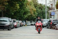 Rowerzysta dziewczyna w skórzanej kurtce na motocyklu jedzie w mieście obraz stock