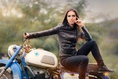 Rowerzysta dziewczyna w skórzanej kurtce na Retro motocyklu zdjęcie stock