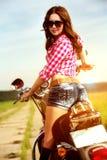 Rowerzysta dziewczyny obsiadanie na motocyklu zdjęcie royalty free