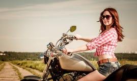 Rowerzysta dziewczyny obsiadanie na motocyklu Zdjęcia Royalty Free