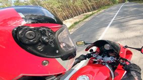 Rowerzysta jedzie czerwonego motocykl na drogowym, będący ubranym hełm zbiory wideo